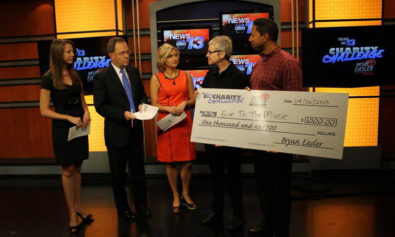 Anne Coombs of Give To The Music accepting a BIG check on WLOS
